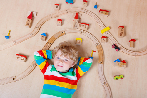 Boy laying down between play railroad tracks