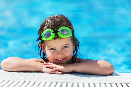 boy on side of pool with googles on his head smiling