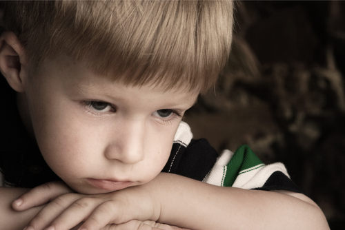 boy with chin on arms looking sad