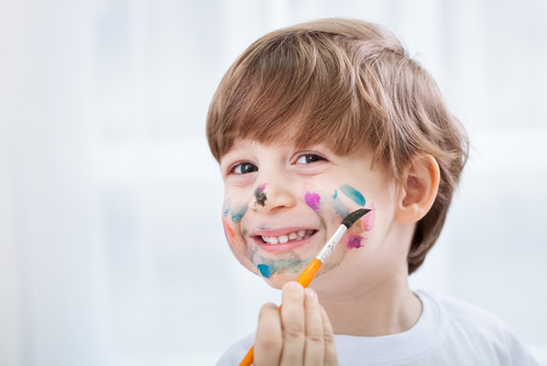 boy smiling with paint brush and paint on his face
