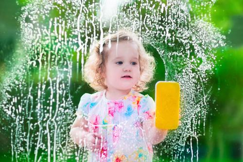 girl washing window with sponge