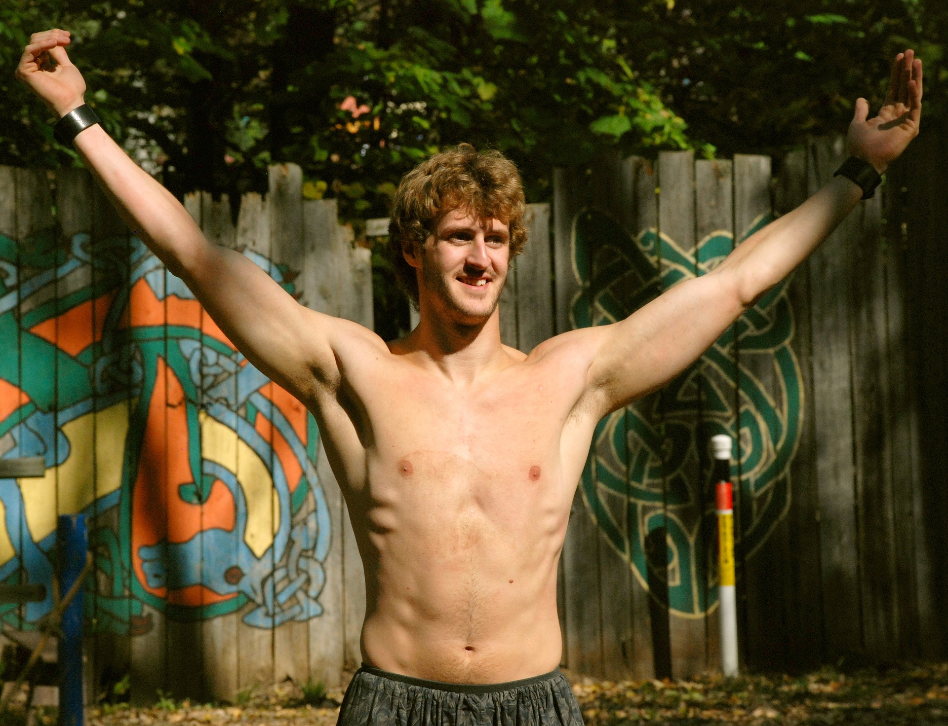 shirtless man with raised arms smiling