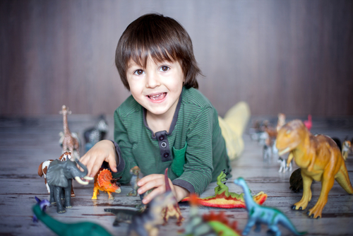 little boy smiling playing with dinosaur toys
