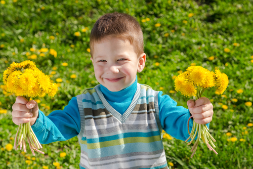 boy holding flowers in both hands smiling