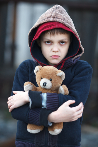 Boy holding teddy bear tightly.