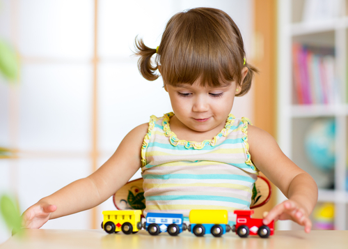 Little girl in play therapy playing with a train.