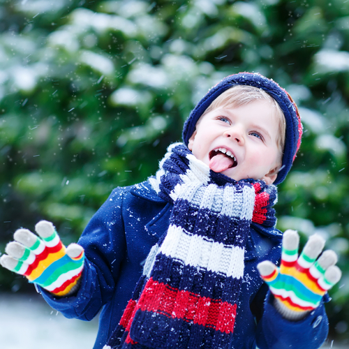 Child catching snowflakes on his tongue