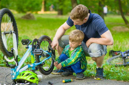 man with son working on his bicycle