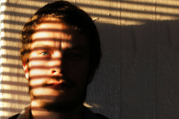 young man looking through blinds