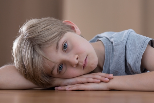 child with his head down on the table