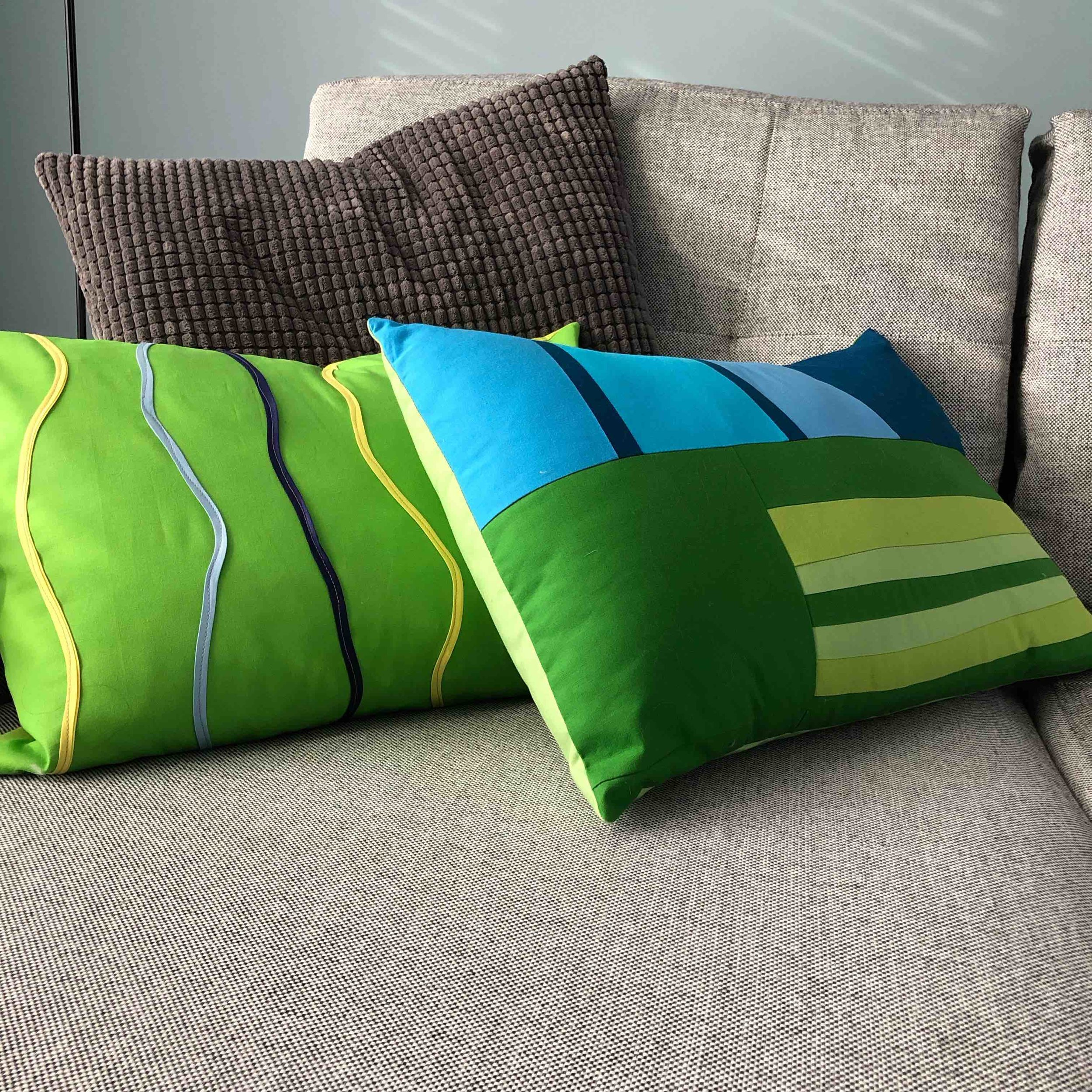 Contours  pillow on the left with bias tape.  Summer Prairie  pieced in blues for they sky and greens for the grasses on the right.