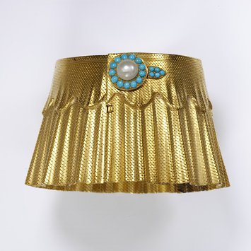 England, c 1860   Gold with turquoise and pearls   'Manchette' or cuff bracelets became fashionable in France in the 1850s and 60s and then spread to England. In a letter to her daughter, the Princess Frederick William of Prussia, in 1861 Queen Victoria described a wedding anniversary gift of 'a beautiful bracelet which he got at Coburg- from Gotha- a large elastic gold bracelet like a cuff – and so pretty'.   The gold on this bracelet is textured to look like cloth. A buttonhole and button are formed of the turquoise and pearl fashionable in the period.   V&A Museum