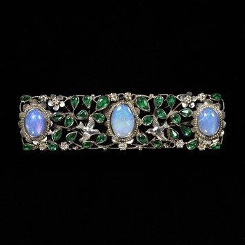 Gaskin, Georgie Cave, 1868 – 1934 (designer)   Brooch, Silver wire, opals, glass imitating emeralds   V&A Museum