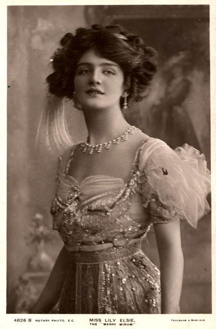 Edwardian lady. Note the dangling, flowing earrings and the aigrette. She is also wearing a 'fringe' necklace, a style popularised by archaeological revival.