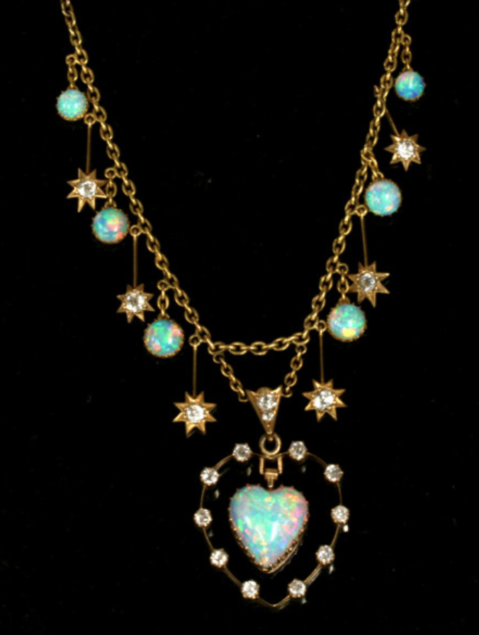 Made in 15ct gold at the start of the 1900's, it is set with 6 drop opals with one superb heart shaped opal at the bottom, which is surrounded by 10 diamonds. With a further 8 diamonds along the chain, the diamonds total 0.86 carats, and match so well with the opals.   The entire length measures 38.5 cm, and this is a truly spectacular piece that will always be cherished.  Source: Kalmar:  www.kalmarantiques.com.au/product/antique-opal-and-diamond-necklace/