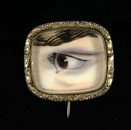 Miniature on ivory, c. 1830's. Hand-painted miniature of a left hazel eye on ivory in heart-shaped pendant. Eye miniatures or Lovers' eyes were Georgian miniatures, normally watercolour on ivory, depicting the eye or eyes of a spouse, loved one or child.   PUBLIC DOMAIN