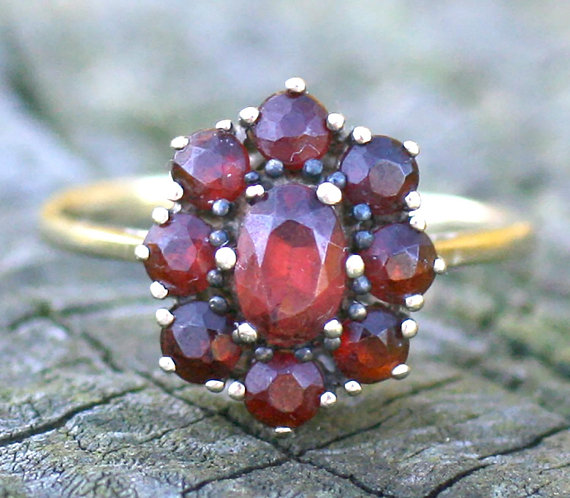 Wonderful vintage or antique 8 karat (hallmarked) yellow gold and (Bohemian) garnet cluster ring. It has an à jour setting which means the light shines through it beautifully. There are 9 deep, dark red rose cut garnets in total, one large central one surrounded by 8 smaller.