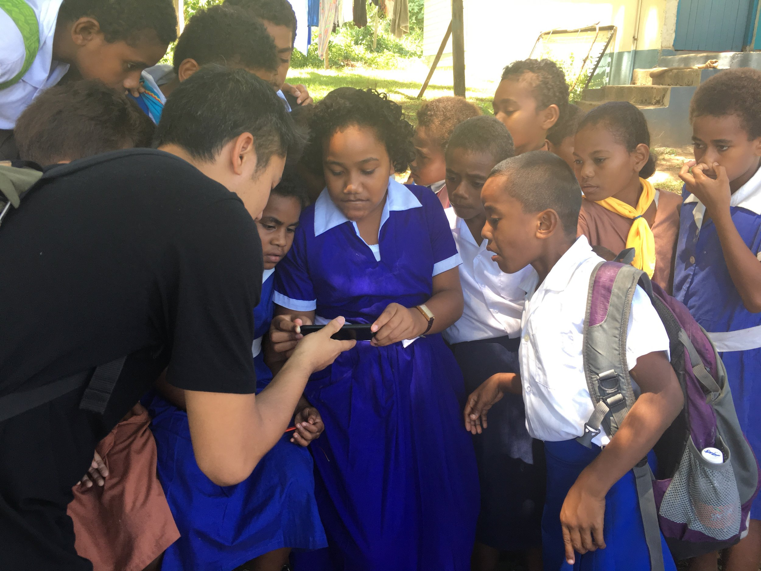 Producer Tash Tan of S1T2 sharing an AR demo to school students on a LAUNCH Legends field reporting trip to Fiji photo by Rob Oliver