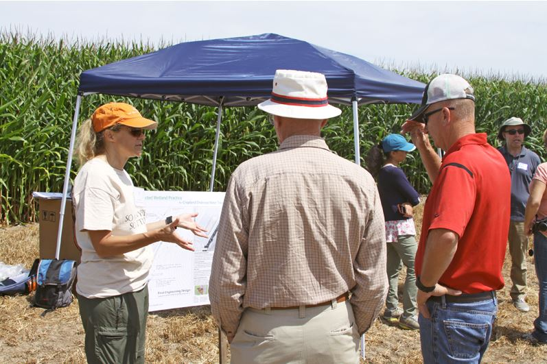 Jill Kostel, the project manager, talks with expo attendees about constructed wetlands at one of the tour stops.