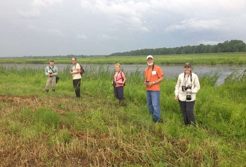 A bird survey group led by Paul Sweet braves the impending rainstorm to search for birds in the wet meadow and prairie habitats of the Refuge's interior. Photo by Vera Leopold.
