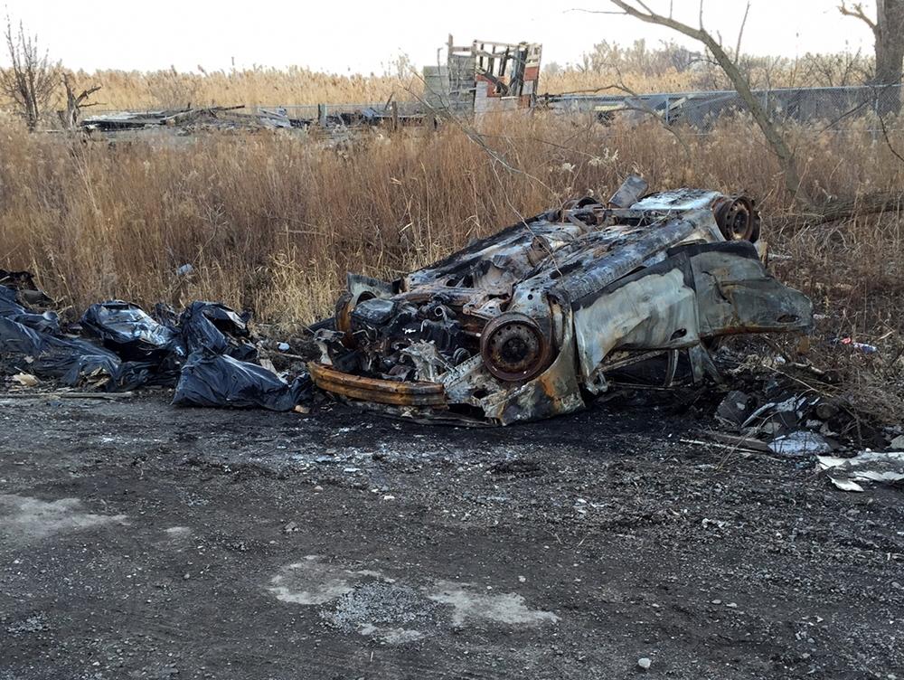 The burnt-out hulk of a car, an old foundation, and other debris will need to be removed to restore Indian Ridge Marsh.