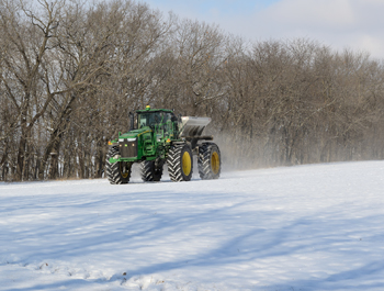 Spreading seed over the snow to begin restoring rare prairie habitats at Hickory Hollow.