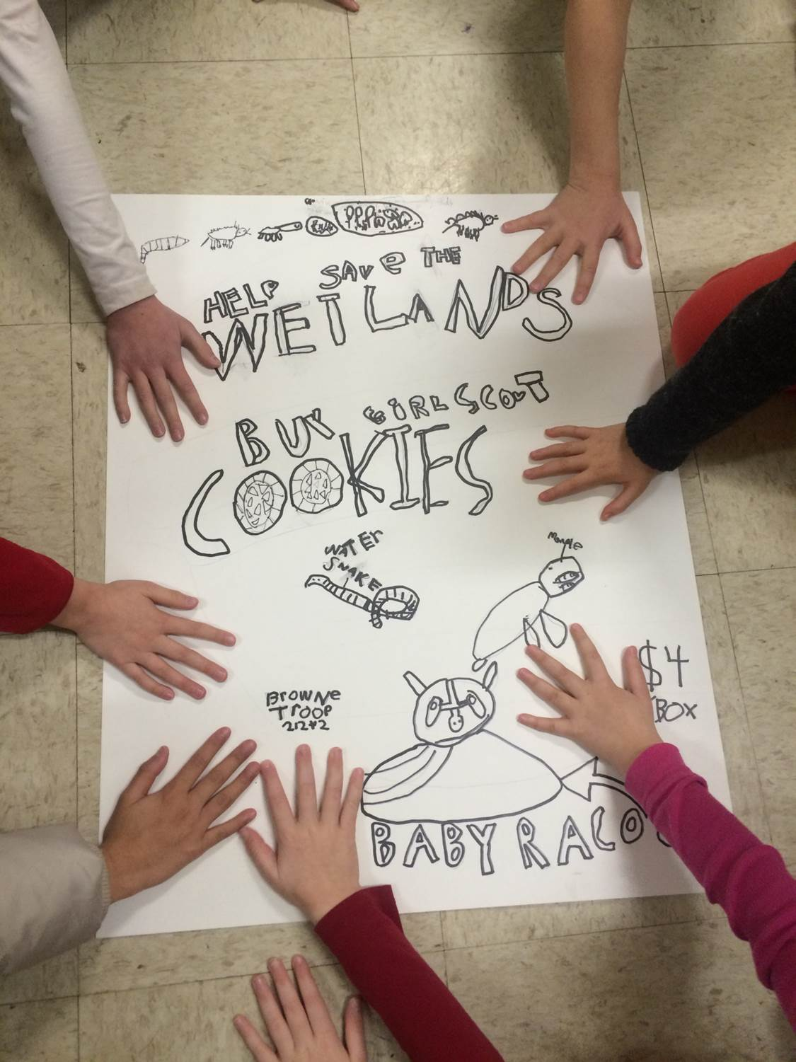 The Rainbow Troop displays one of the many posters they created for their cookie sale booths.