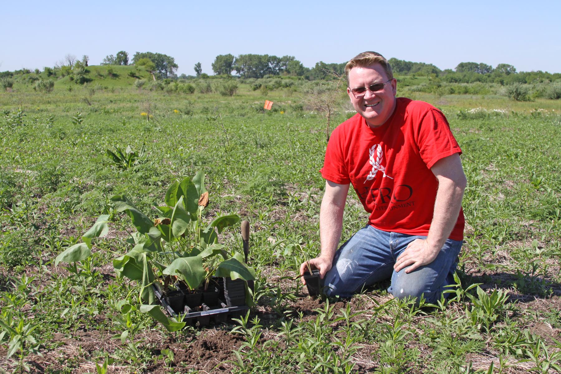 A Harrah's HERO volunteer smiles while planting prairie dock.