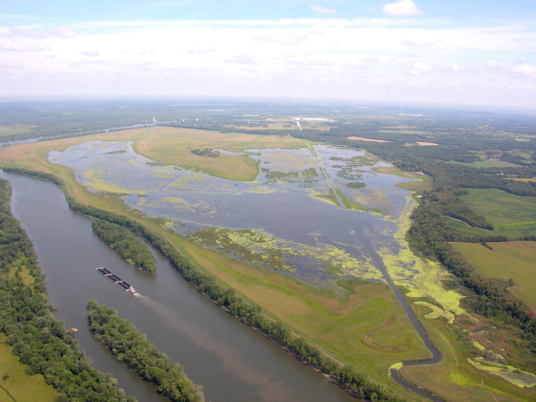 An aerial photo shows the Hennepin & Hopper Lakes system and rich restored habitat at the Dixon Waterfowl Refuge along the Illinois River (visible along the left).