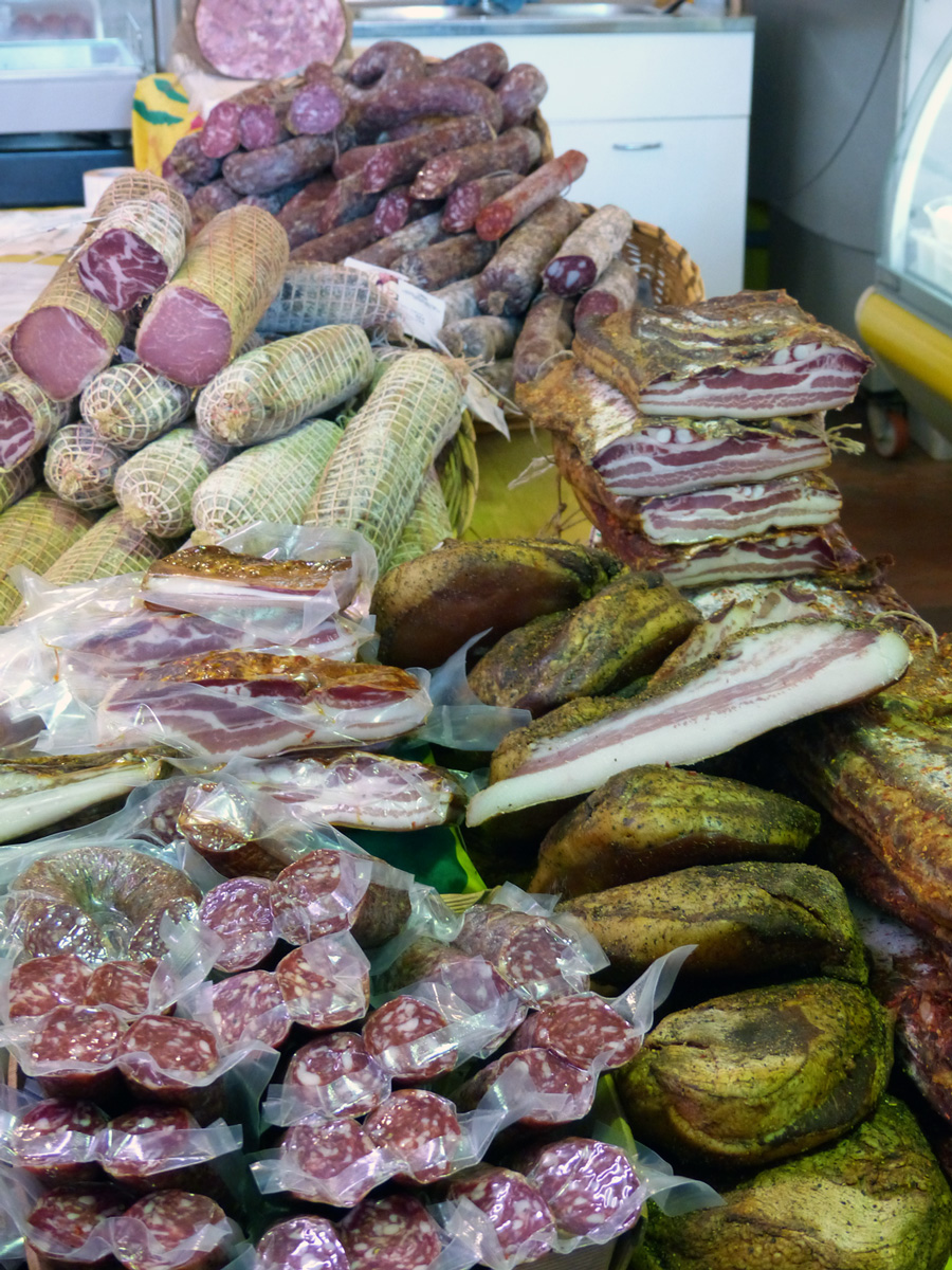 Dry cured meats in a small but fully packed local market Rome, Italy.