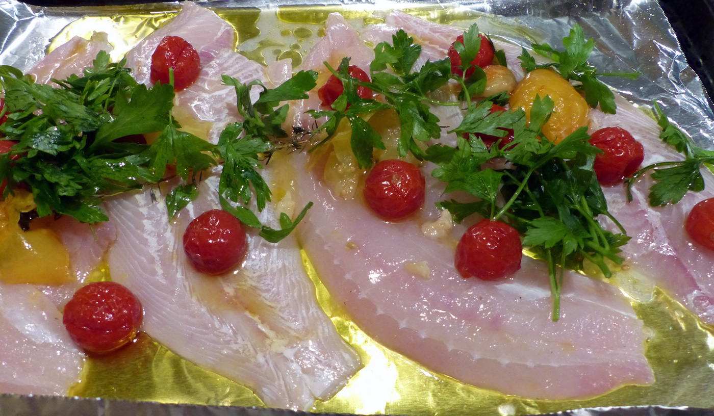 On an aluminum lined baking sheet, place the fillets, drizzle with oil, sprinkle with salt/pepper and top with tomatoes, parsley, garlic and onion.