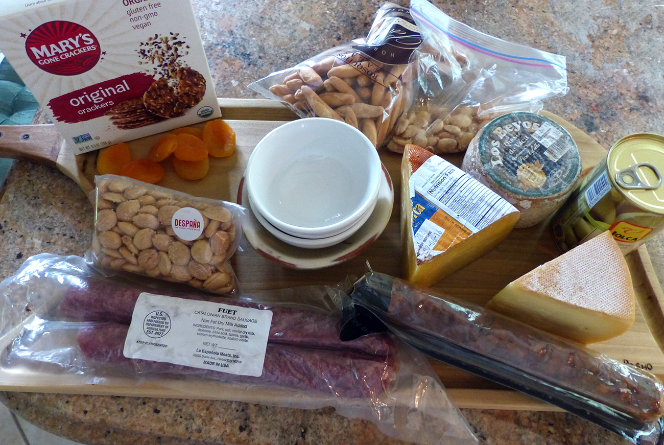 Here is 2 types of dry cured sausage, 3 types of cheese, Marcona almonds, olives, dried apricots, gluten free crackers and short bread sticks.