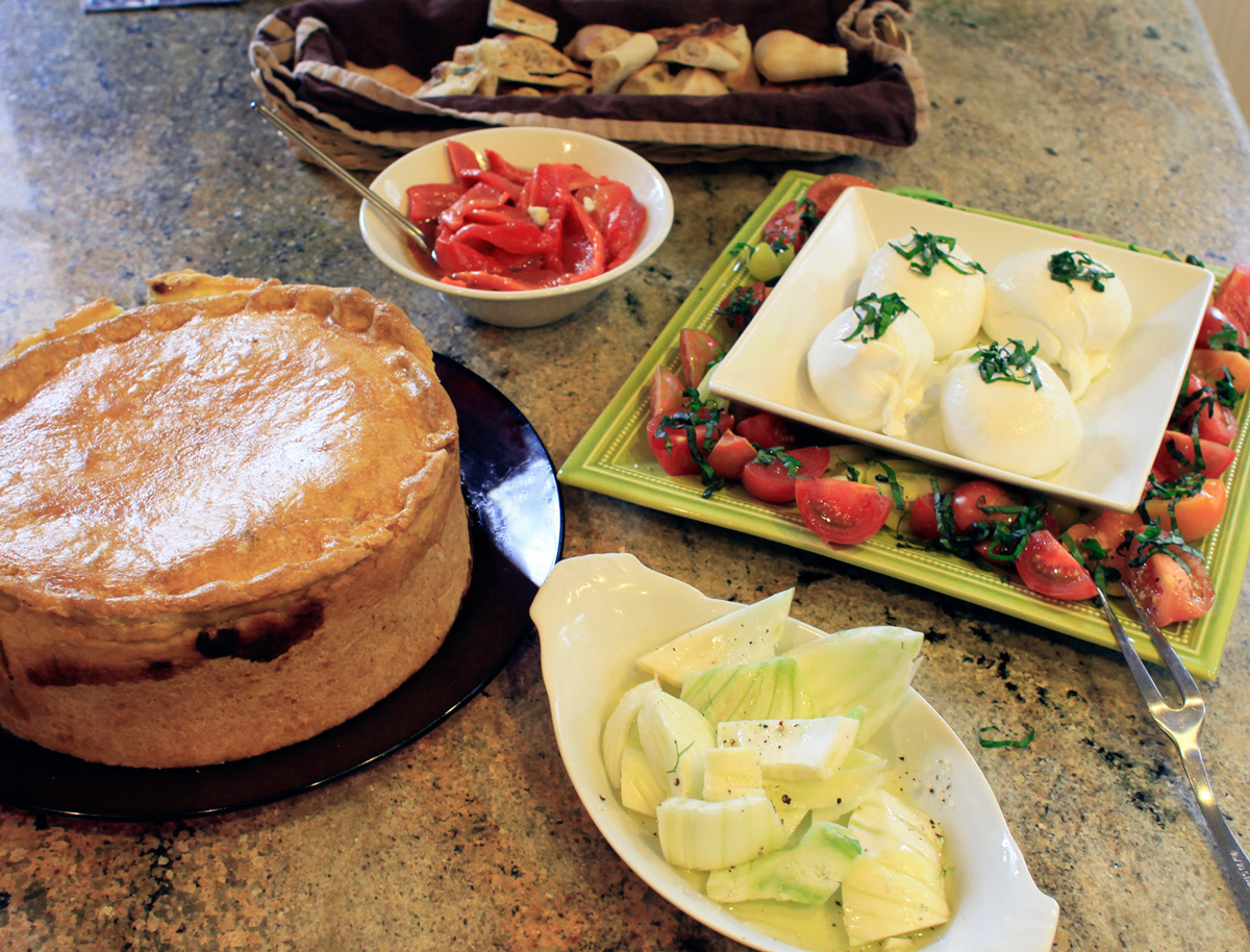 Our line up of apps one year.  Roasted red peppers, burrata with fresh tomatoes/basil, fennel with coarse salt/pepper/oil and the of course, the towering Pizza Rustica.
