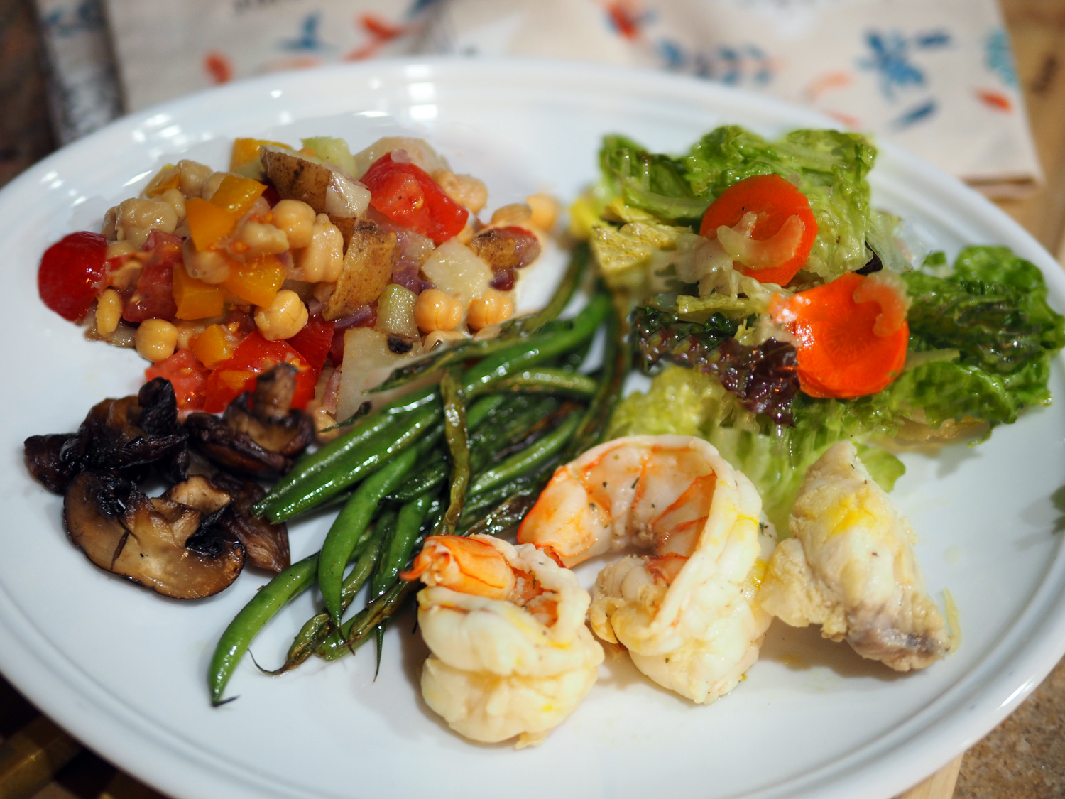 Simple green salad with carrots/red onion, sautéed Haricot Vert, sautéed Cremini mushrooms, Shrimp & Monkfish in a saffron broth and our star potato/chick pea salad.