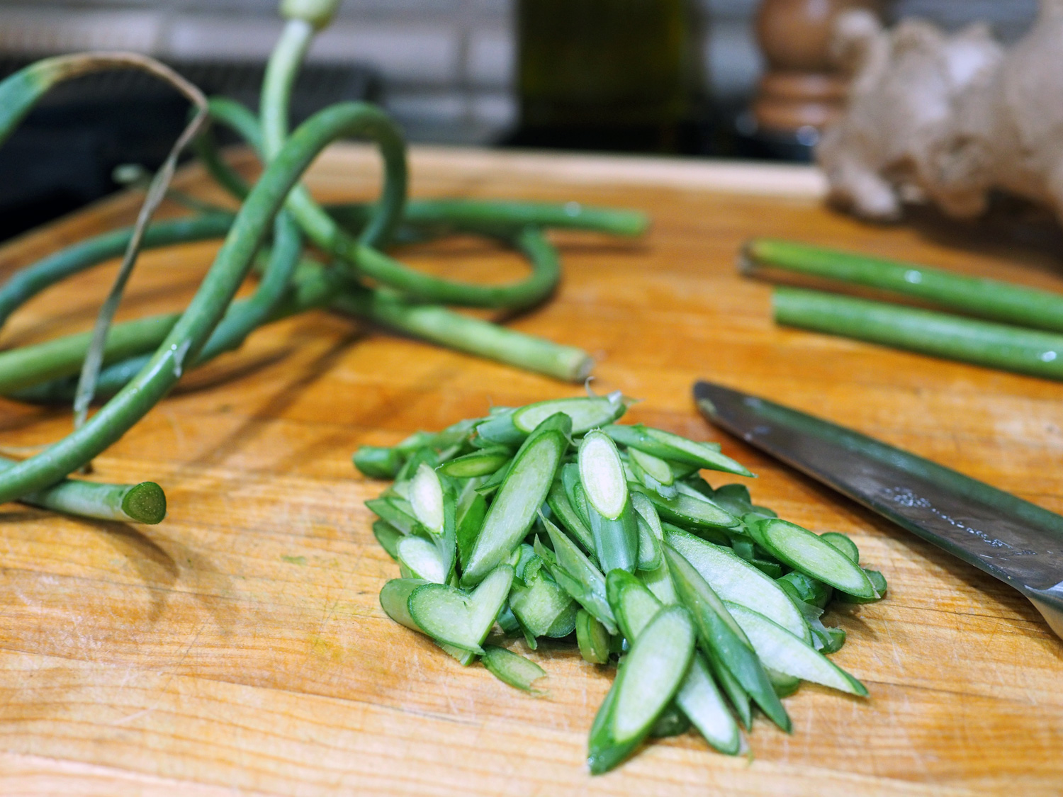 Thinly slice the garlic scapes. I like the diagonal, as it gives more surface area when sautéing. Also, cut off the end of the garlic scape and toss out, as this part, much like that of an asparagus, can be tough.