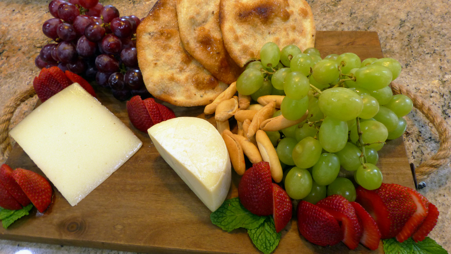 Cheeses with strawberries, grapes, mini  bread sticks  and  Tortas de Aceite  (Sweet Olive Oil Crackers).