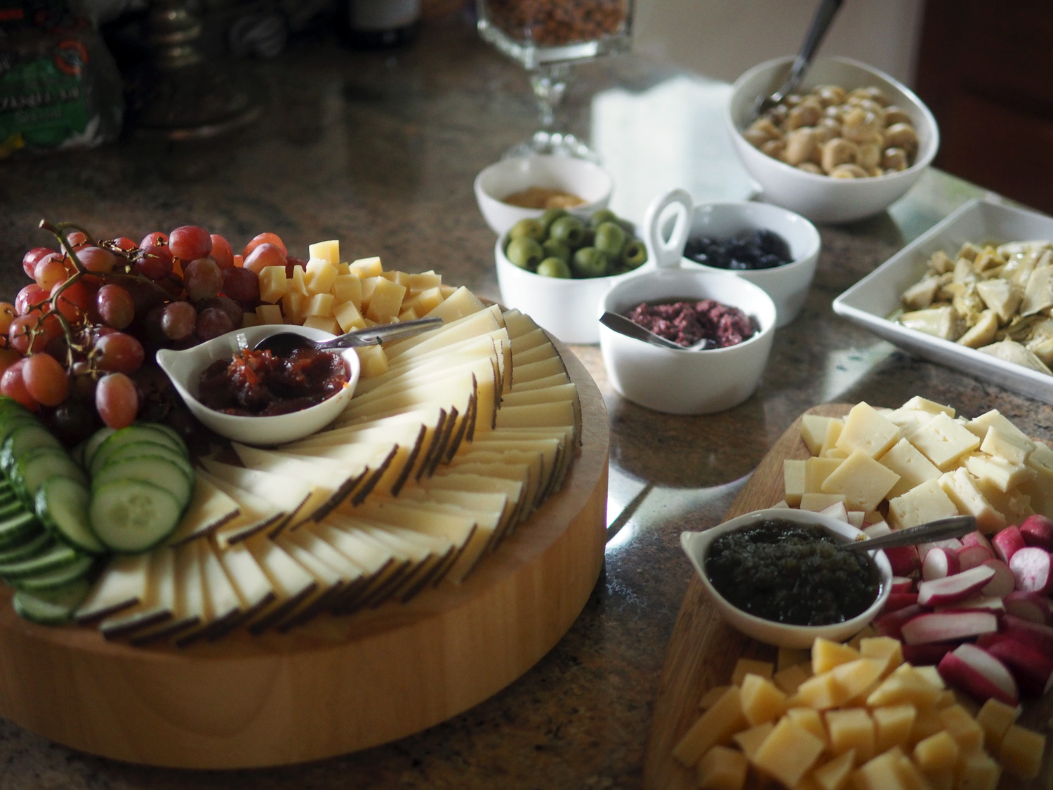 Abundant cheese platters with jams and grapes, cucumbers and radishes.