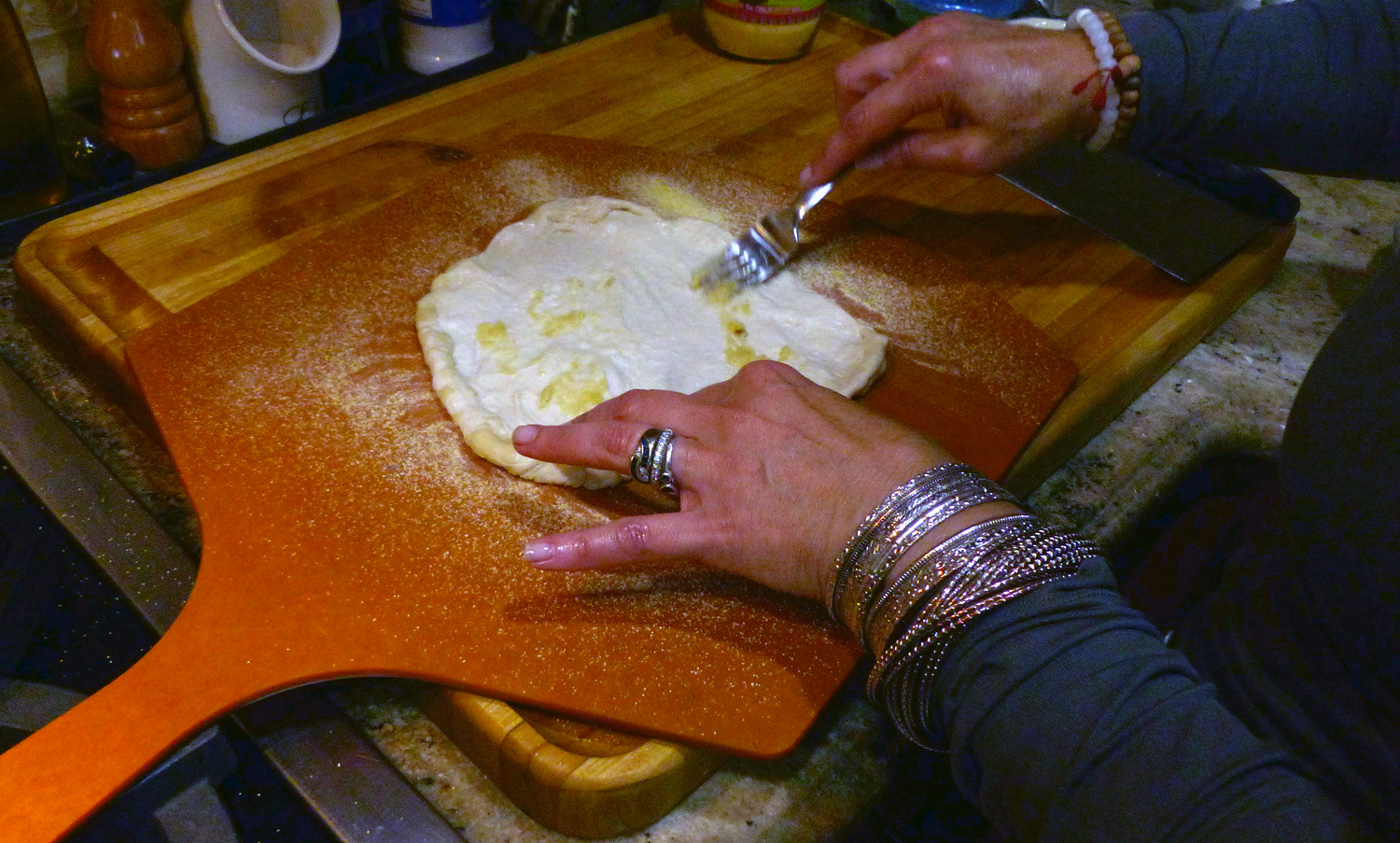 Spreading roasted garlic mash on the dough