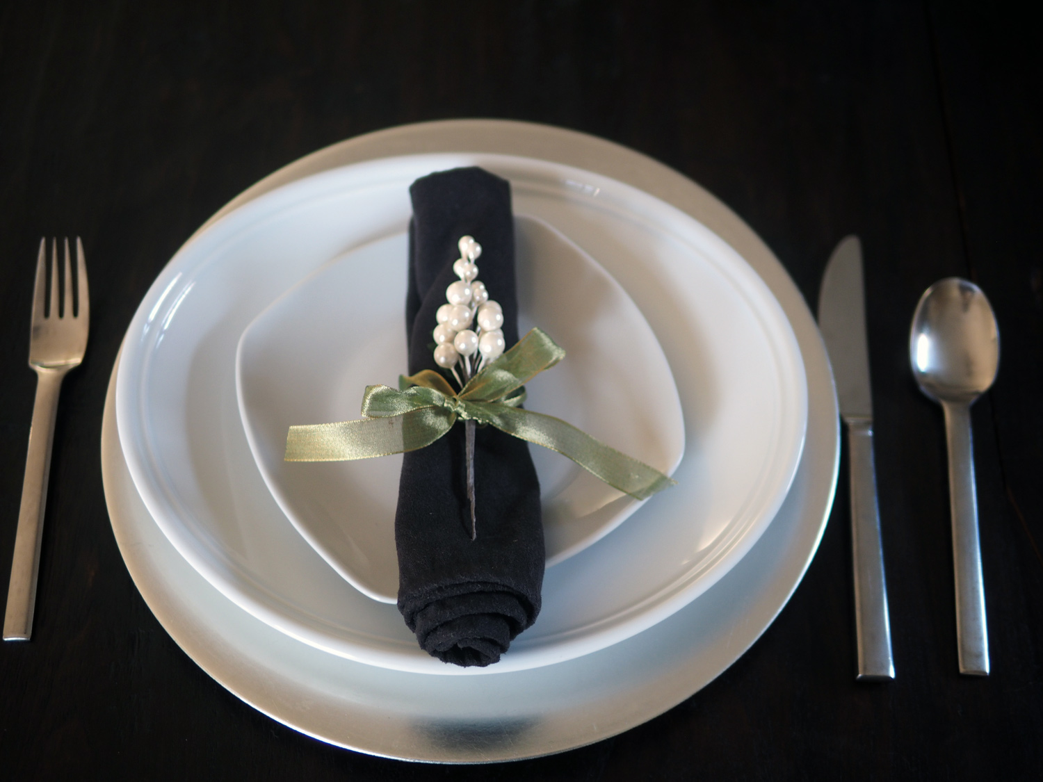 Once you have rolled the napkin up, tie a ribbon, knot it, place an ornament down and tie a bow. Place in the middle of the plate.