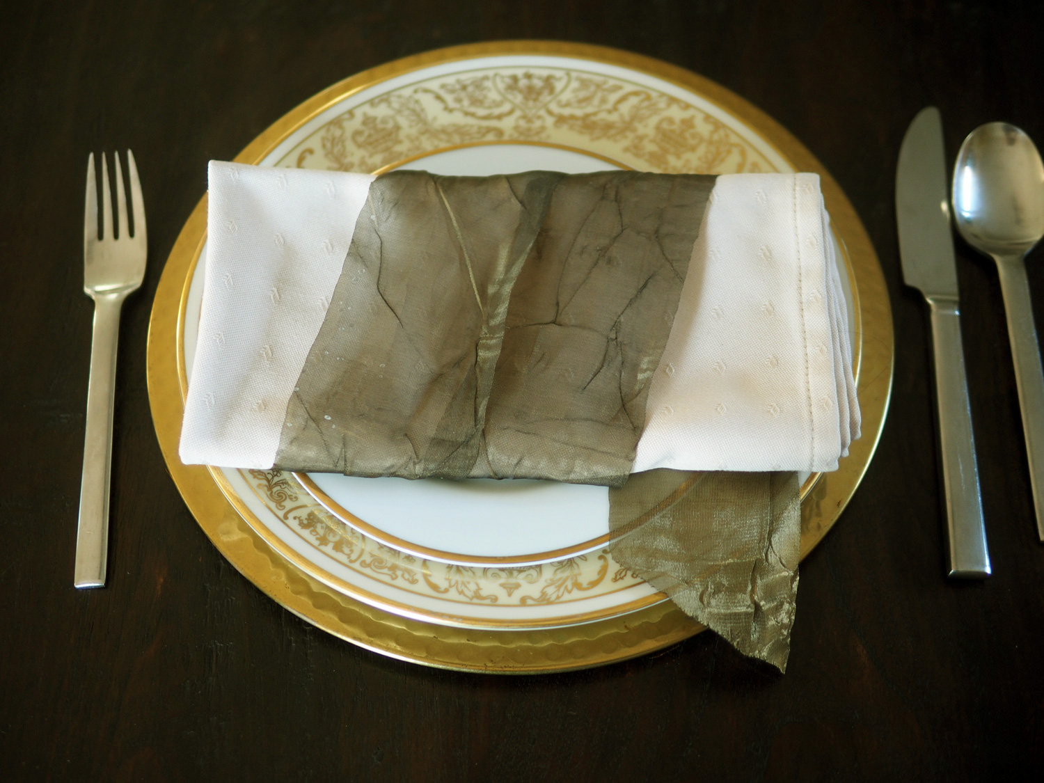 The simple rectangle napkin has a more powerful impact with a doubled ribbon wrap tail peeking out.