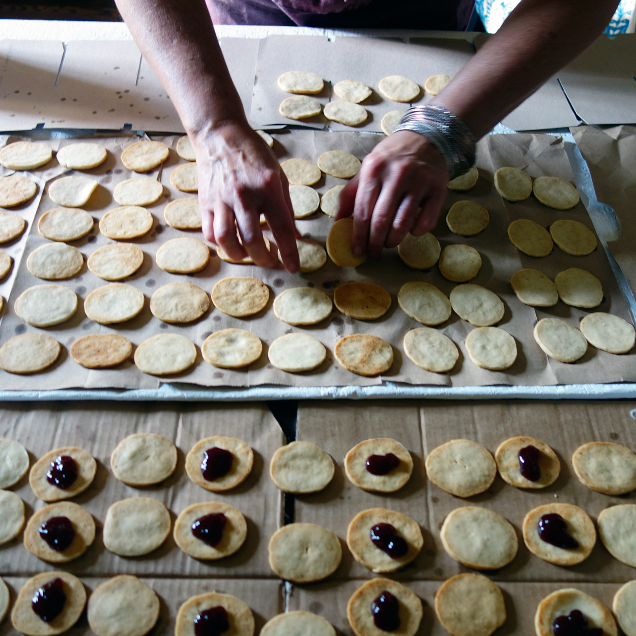 After they are lined up, turn one row over so you are filling the baked side with jam. Then the outside of the cookie looks nice when sandwiched together.   Photo credit:    asithappens.format.com