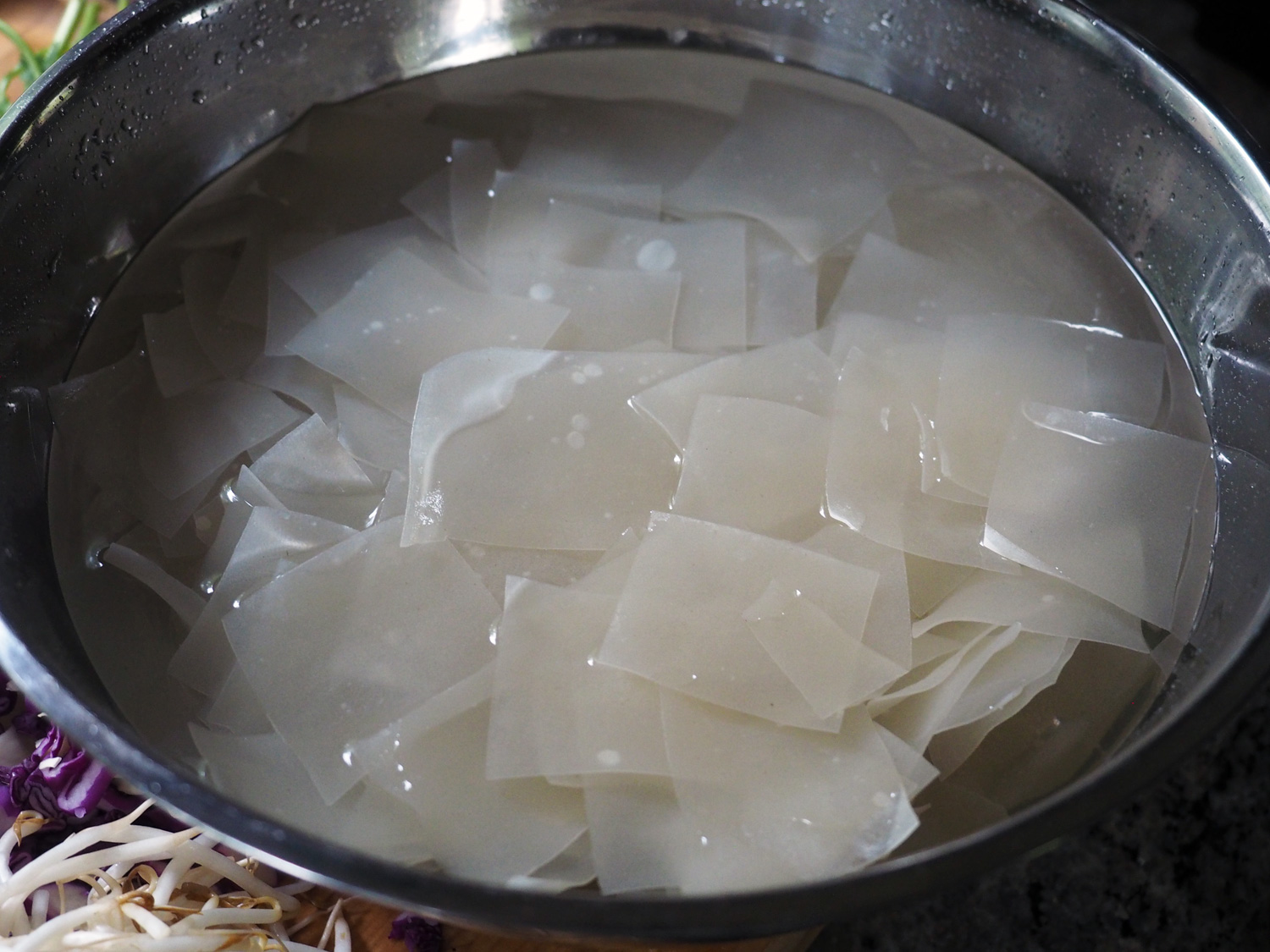 Rice noodle rags soaking in warm water.