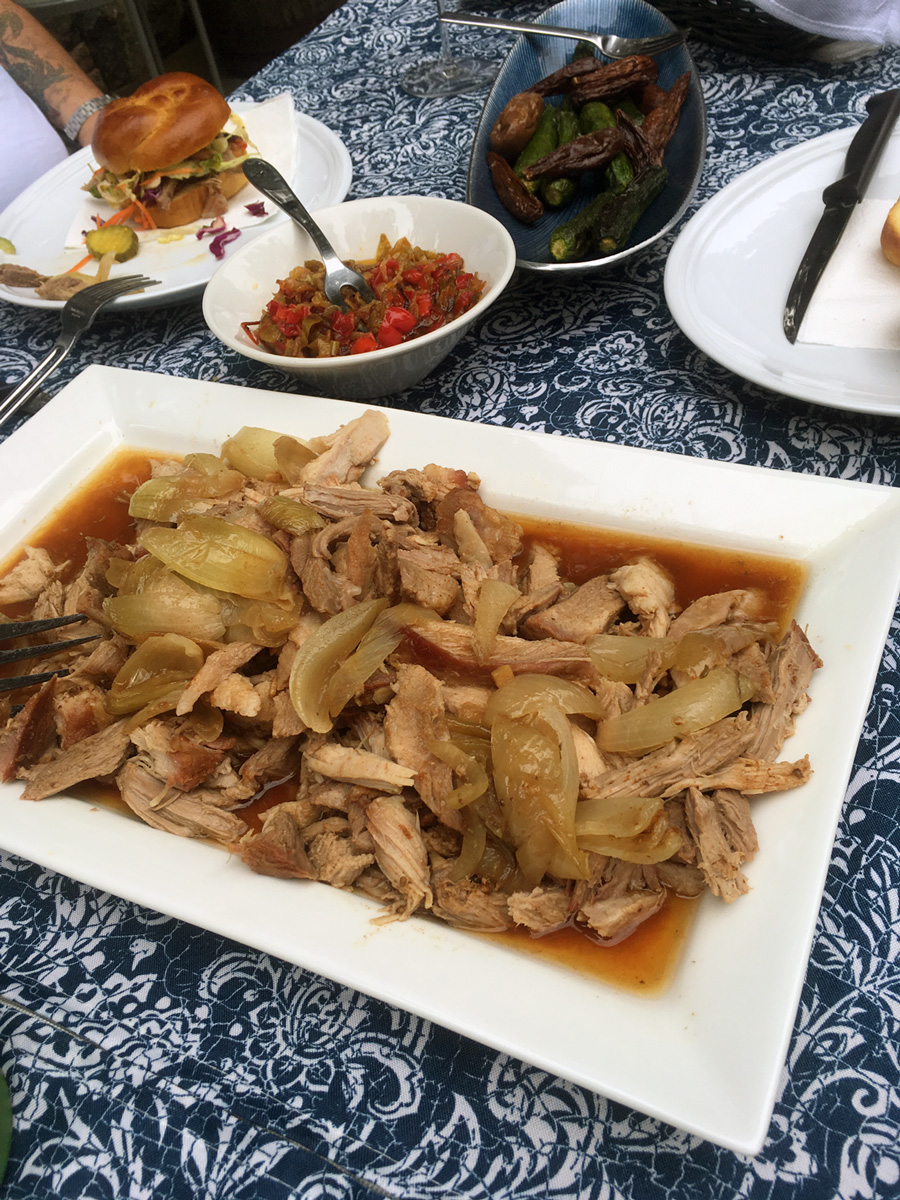 A platter full of pork with luscious juices and soft, flavorful onions.