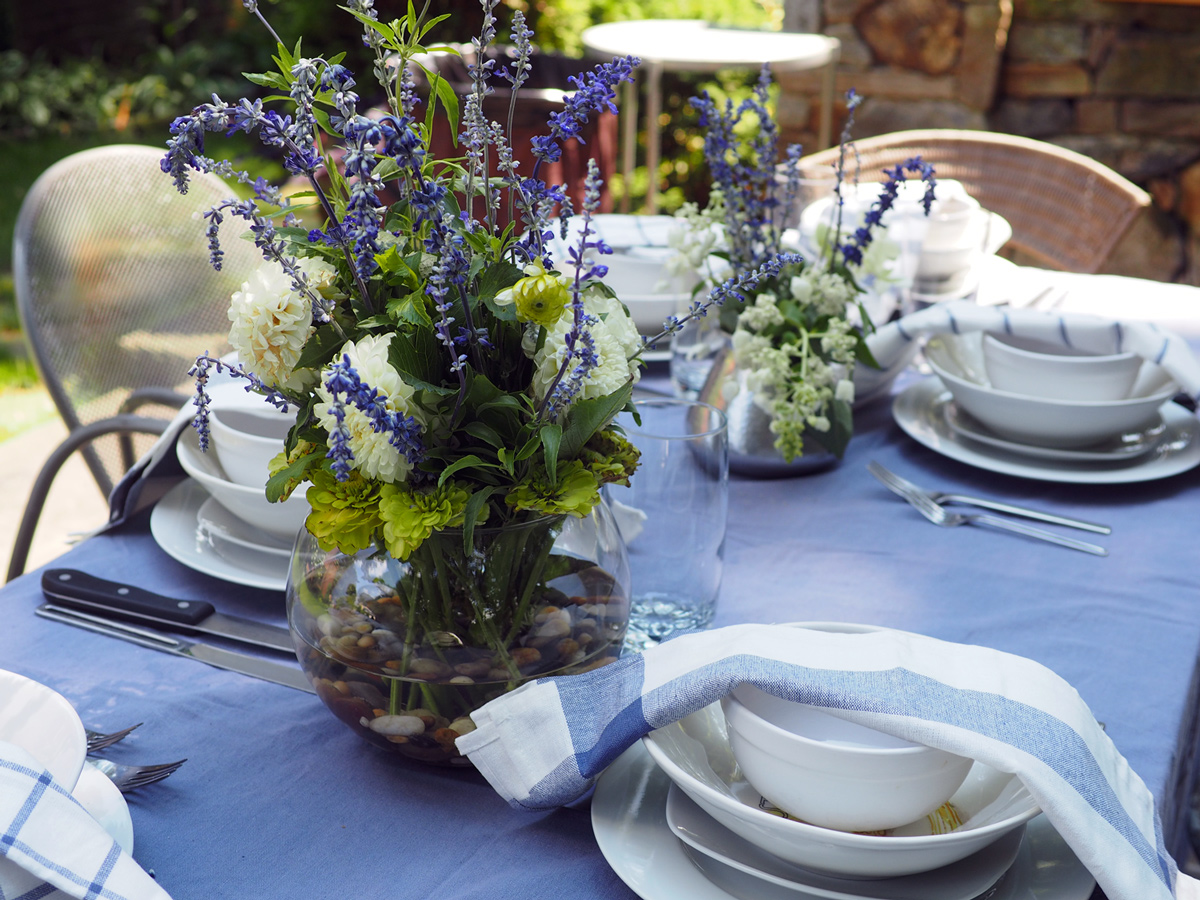 White plates with cotton napkins keeps this simple while the florals takes a early evening dinner to a   dreamy blue elegant table  .