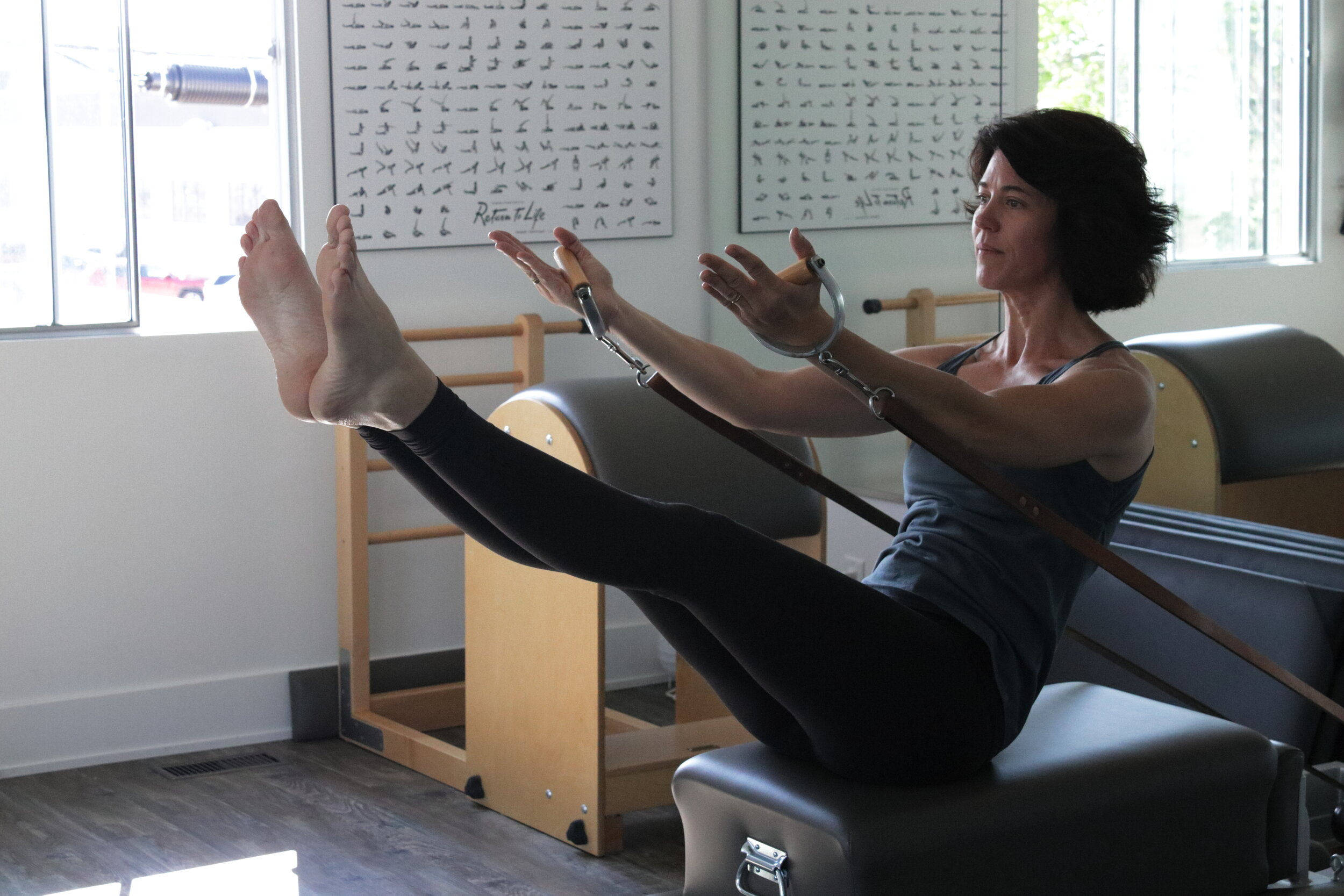 Julie, our senior teacher at Aligned Pilates practising her Teaser.