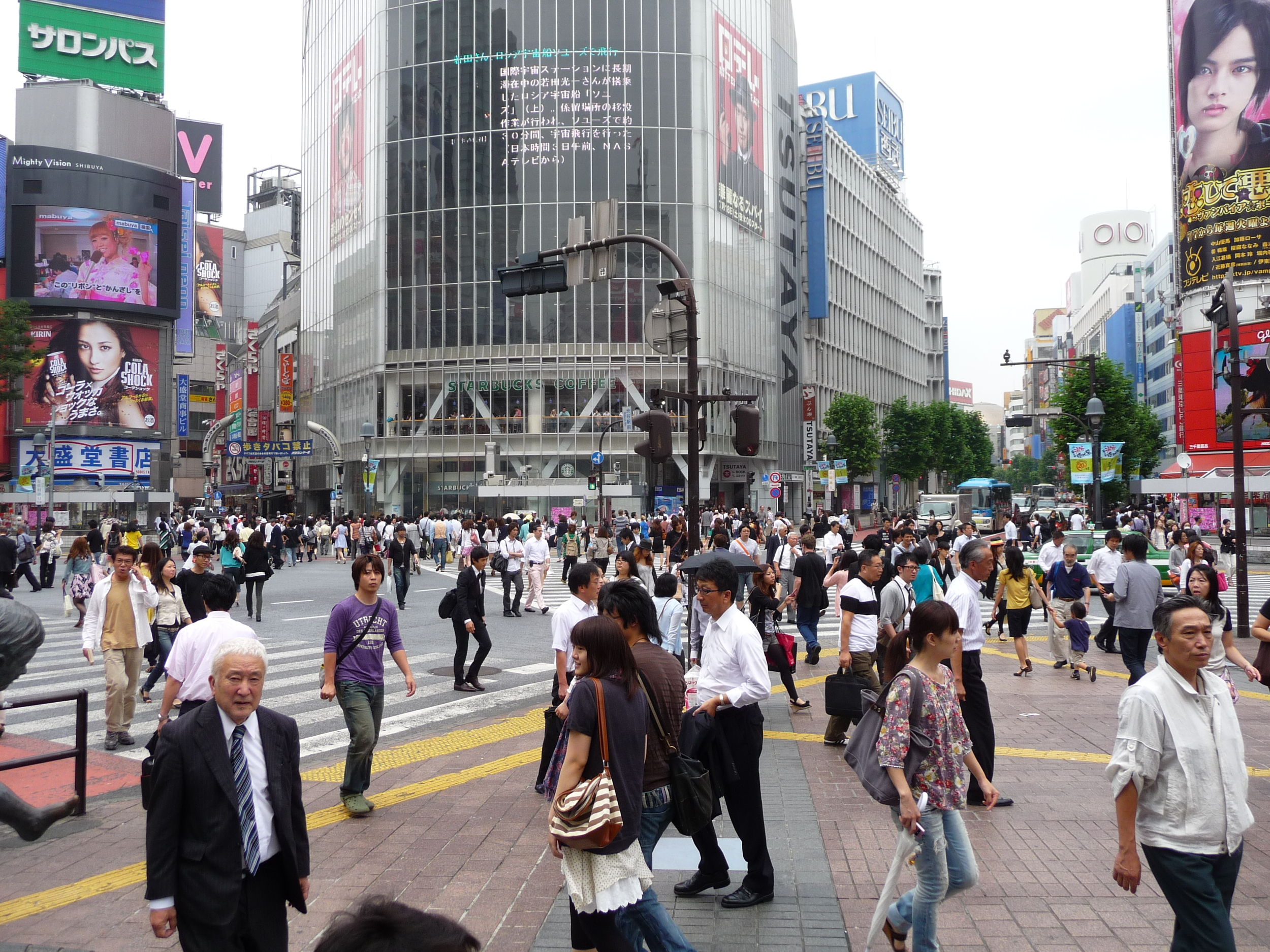 """Tokyo's famous Shibuya """"Scramble crossing"""" - five streets, plus a busy metro station, dozens of buses, and multiple shopping arcades. Said to be the busiest single spot on Earth - incredible for people-watching ... from a safe distance."""