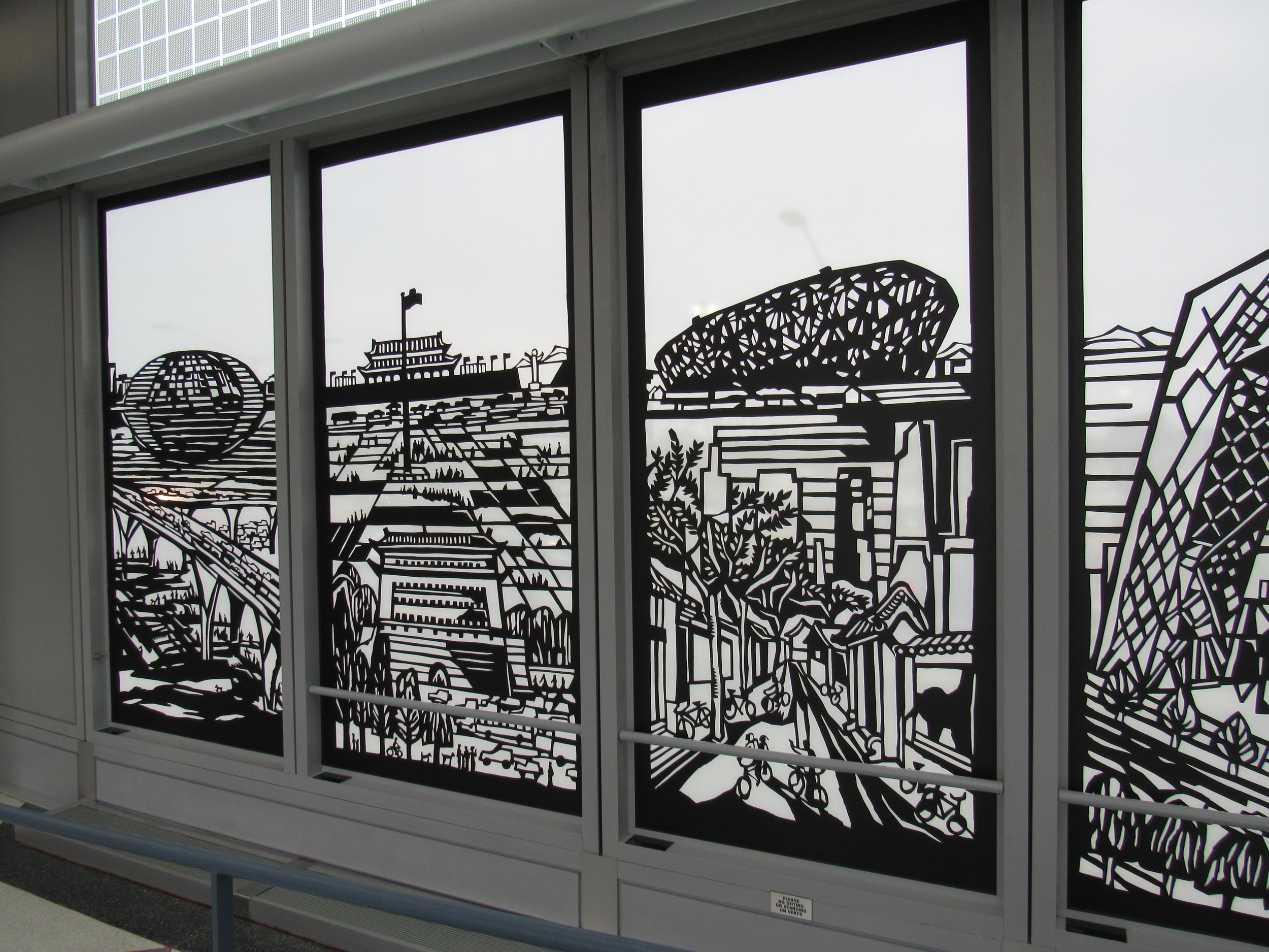 "At the far-eastern end of United's ""B"" concourse, gates b19-20, you'll see a long art installation called ""City Windows"" by Qiao xiaoguang. it is based off traditional chinese papercuts and features scenes from both chicago and beijing. lots of details for kids to hunt for!"