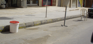 Makeshift parking obstacles placed along the side of a street. (Basma Abdallah)