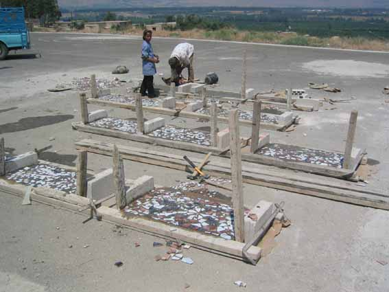 View of the concrete benches under construction showing the ceramic tile designs as created by the students.