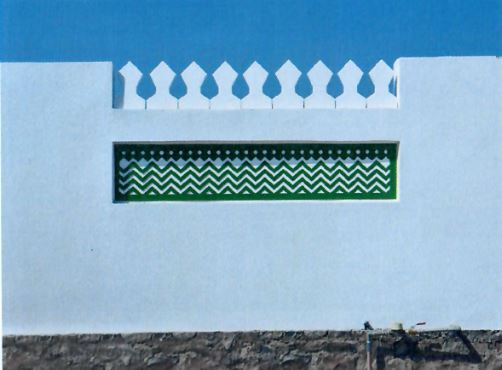 An image of a remodelled wall that is painted white, and that incorporates a stone base, crenellations at its top, and a small mural with a wave-like theme